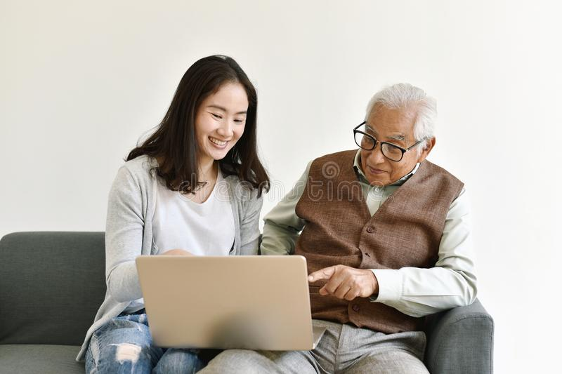 Asian family relationship, Daughter and elderly father using laptop computer together. Asian family relationship, Daughter and elderly father using laptop royalty free stock photography