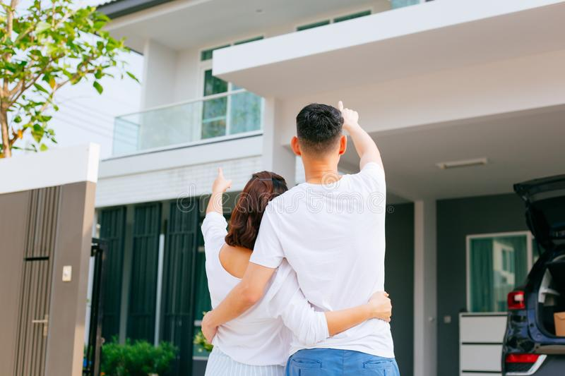 Asian family standing outside with their new house and car carrying boxes. stock image