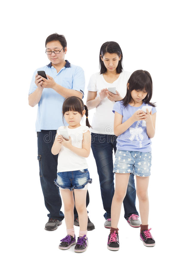 Asian Family standing and using smart phone together royalty free stock photography
