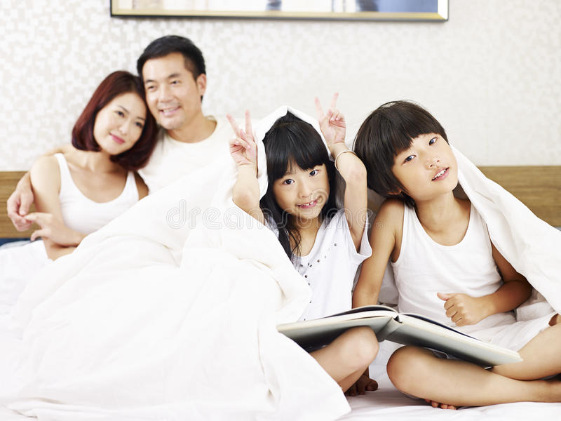 Asian family with two children having fun in bedroom. Asian family with two children having fun in bed royalty free stock photography