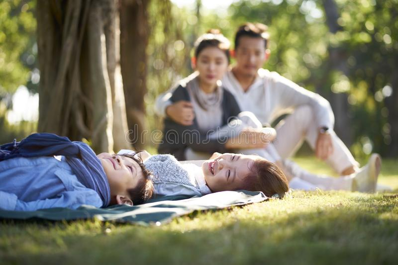 Asian family with two children relaxing in park. Two asian children little boy and girl having fun lying on grass with parents sitting watching in background royalty free stock image