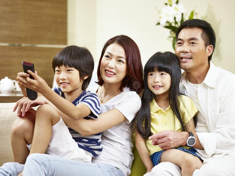 Asian family with two children watching TV at home. Happy asian family with two children sitting on couch at home watching TV royalty free stock image