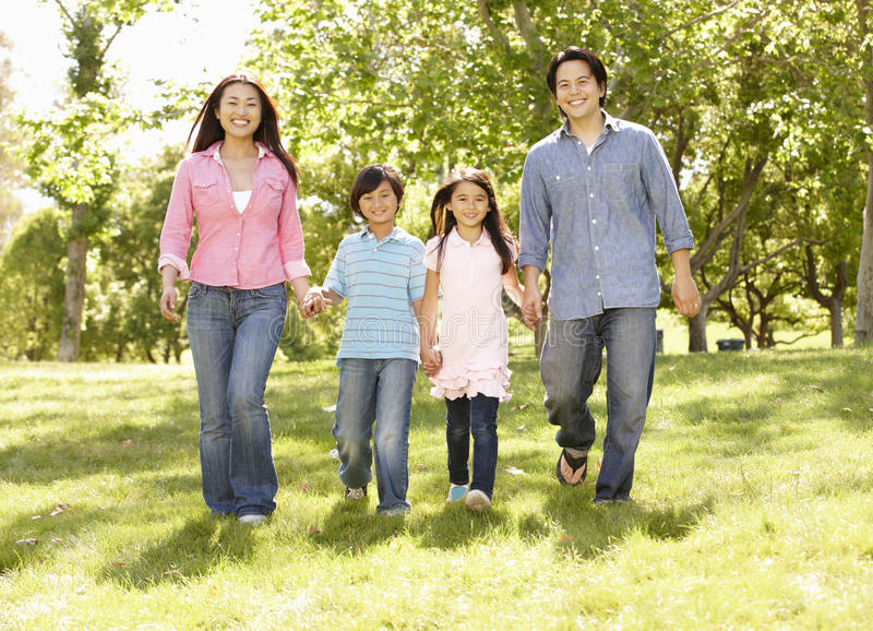 Asian family walking hand in hand in park royalty free stock photography