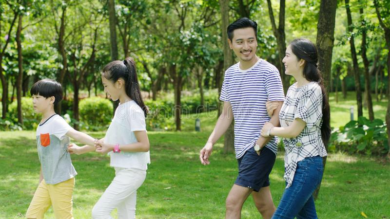 Asian family walking in natural park in summer, smiling and looking at each other royalty free stock photos