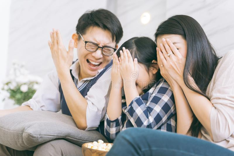 Asian family watching scary movies at home. royalty free stock images