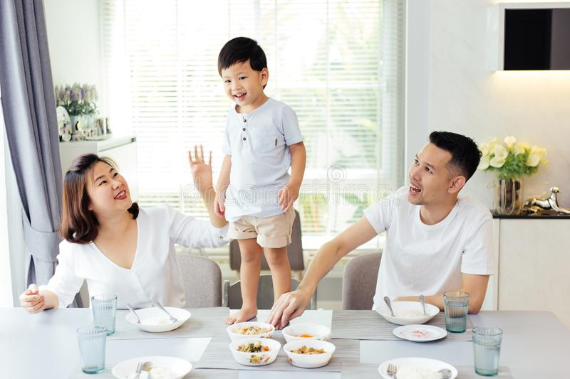 Asian family watching their kid as he is determined and proud to finally stand on the dining table. royalty free stock image