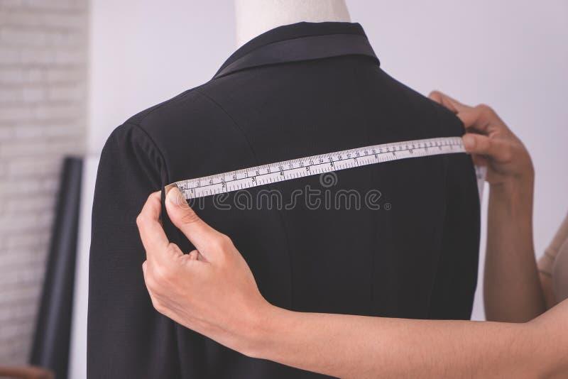 Fashion stylist designer is measuring jacket stock photography