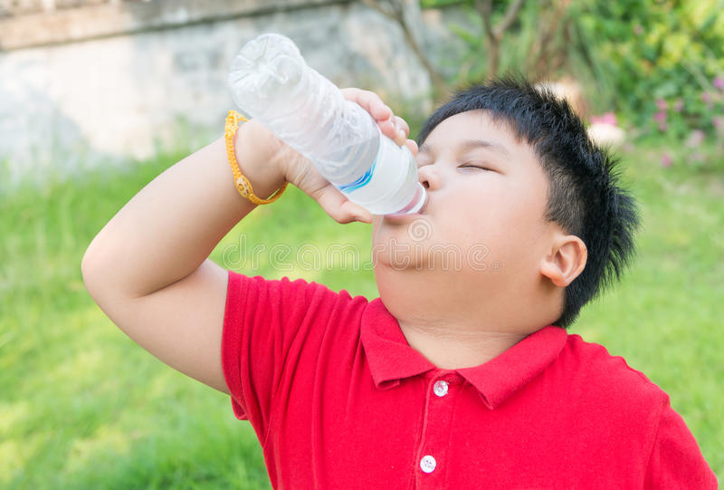 Asian fat boy drinking water. stock photography