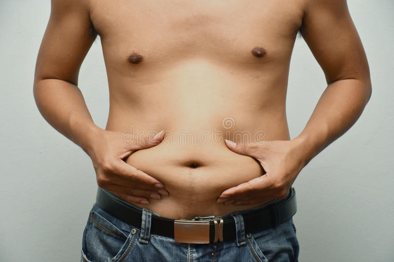 Asian fat man has cholesterol . He shows excess fat of the tummy. By hands use the squeeze at the his tummy. / Photo concept: fat, belly, obesity, cellulite stock image