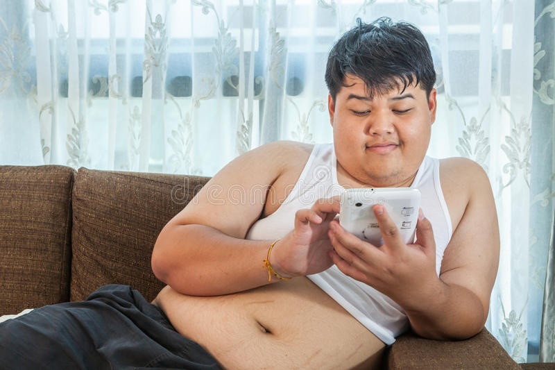 Asian Fat Man Relaxing In The Sofa With The Tablet Stock