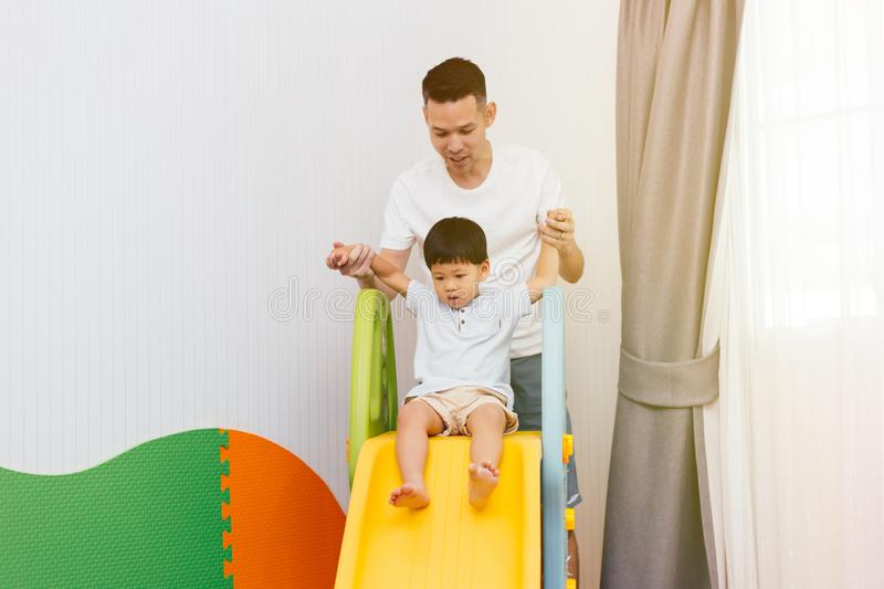 Asian father accompanying child on the playground slider at home. Happy family with toys. stock images