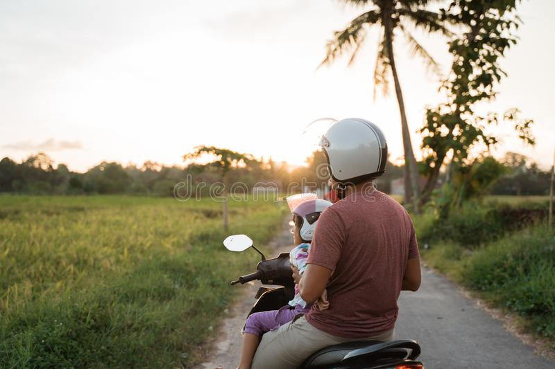 Asian father and child  ride motorcycle scooter stock images