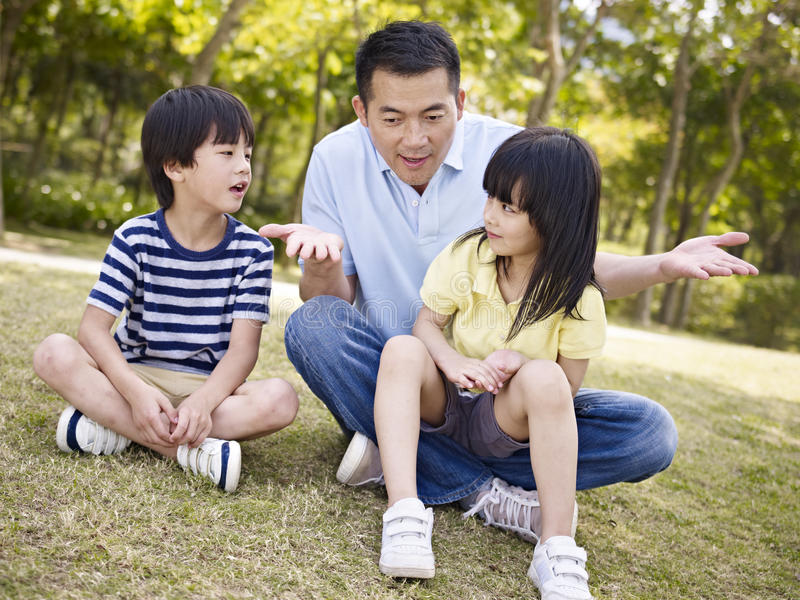 Asian father and children talking in park. Asian father and two children sitting on grass having an interesting conversation, outdoors in a park stock photography