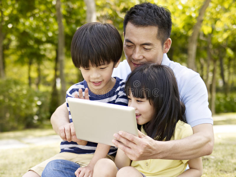 Asian father and children using tablet outdoors. Asian father and two children sitting on grass looking at tablet computer, outdoor in a park royalty free stock photos