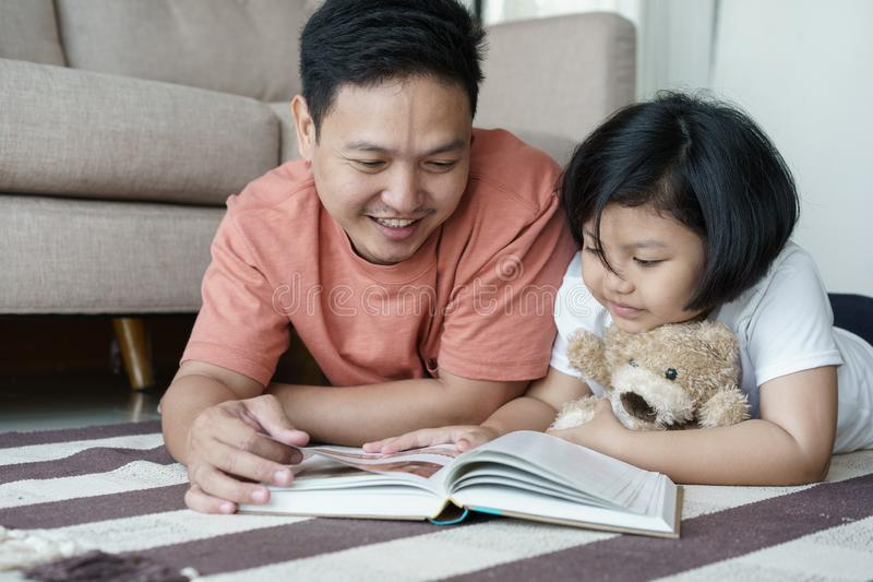 Asian father and daughter read books on the floor in the house, Self-learning concept stock photo