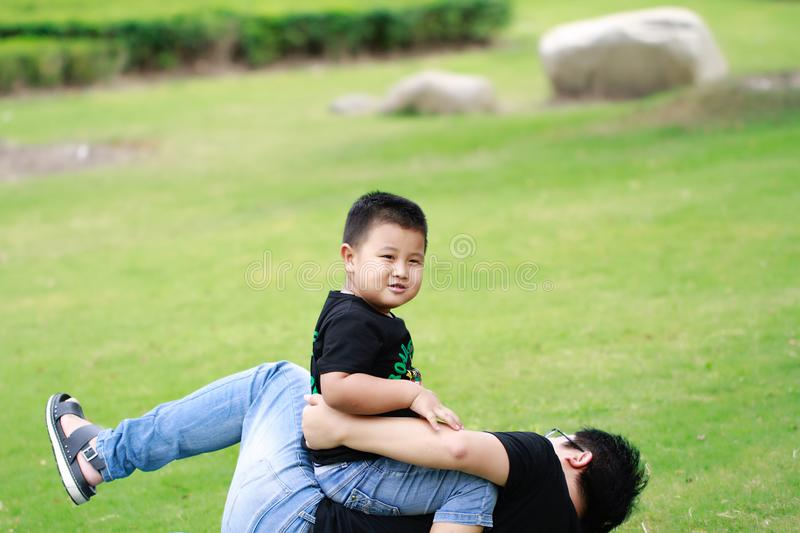 Asian father and son having fun in park. Asian father and elementary-age son enjoying outdoor activity in park,Sitting on daddy`s body royalty free stock images