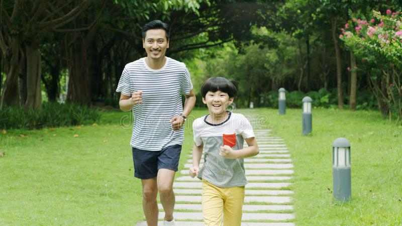 Chinese father runing together with his little son in park in summer royalty free stock images
