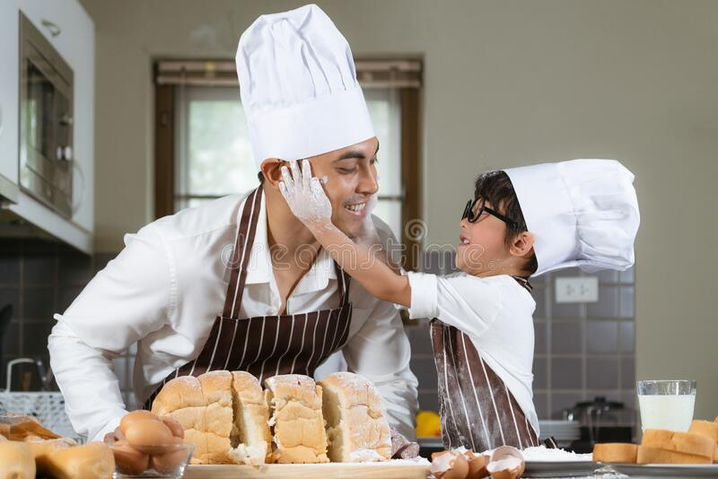 Asian father and son are happy and having fun in the kitchen making bakery royalty free stock photos