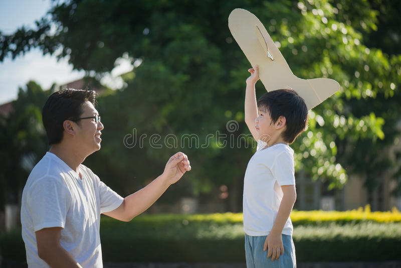 Asian father and son playing cardboard airplane together royalty free stock image