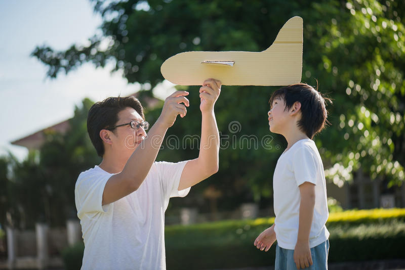Asian father and son playing cardboard airplane together royalty free stock images