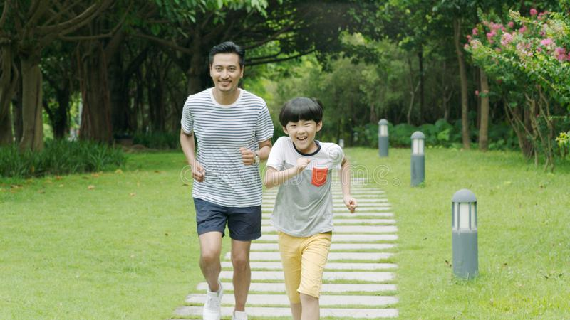 Asian father & son smiling & running in park in summer stock photography
