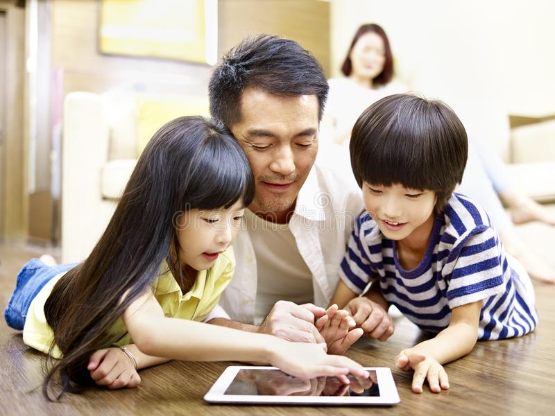 Asian father and two children using digital tablet together. Asian mother and two children lying on front on floor playing with digital tablet while mother royalty free stock images