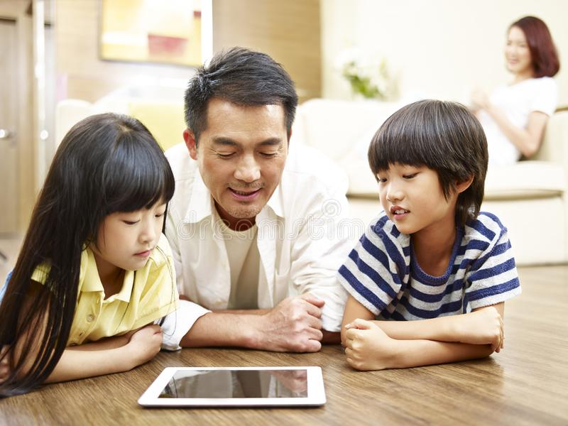 Asian father and two children using digital tablet together. Asian mother and two children lying on front on floor playing with digital tablet while mother stock photo