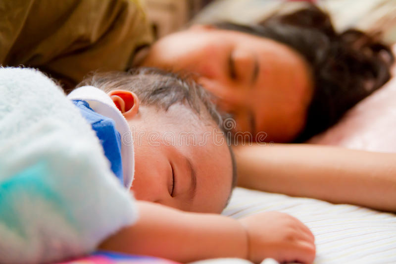Asian female baby sleeping with her mother stock photo
