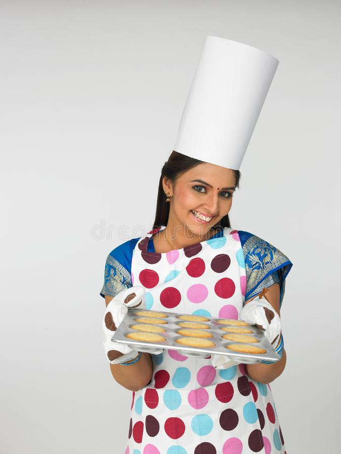 Asian female baker with cookies stock photography