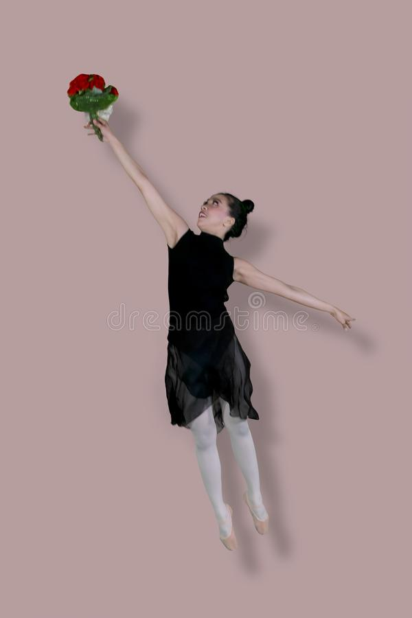 Asian female ballet dancer is dancing with bouquet flower royalty free stock images
