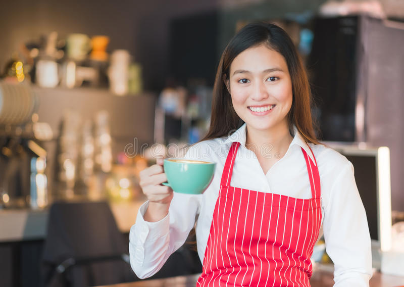 Asian female barista wear red apron holding hot cappuccino coffee cup menu at counter bar with smile face,cafe service concept stock photography