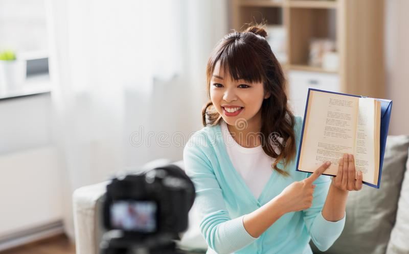 Asian female blogger making video review of book stock photo