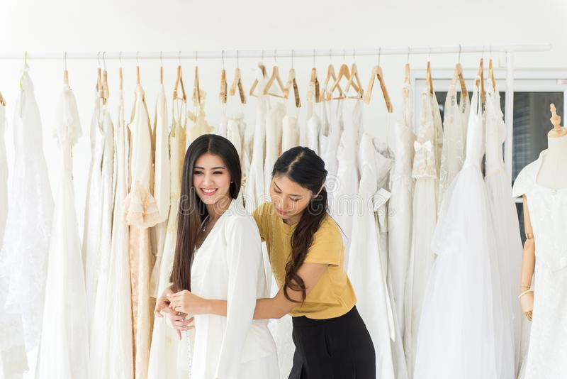 Asian female bride trying on wedding dress,Woman designer making adjustment with measuring tape in fashion studio royalty free stock photos