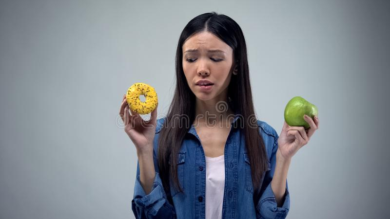 Asian female choosing between sweet greasy donut and juicy green apple, decision. Stock photo stock photo