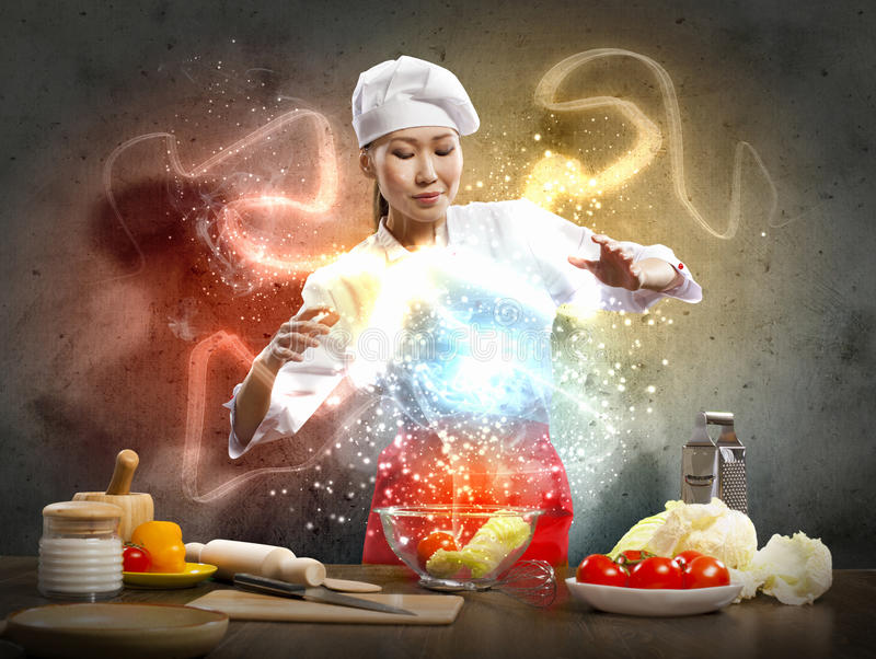Asian female cooking with magic. Against color background stock photography