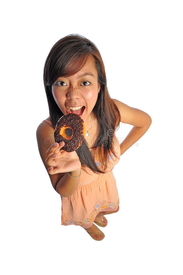 Asian female cute girl trying to eat a donut. Beautiful young Asian Woman engineer picture taken from the top to give a big doll head effect royalty free stock photography