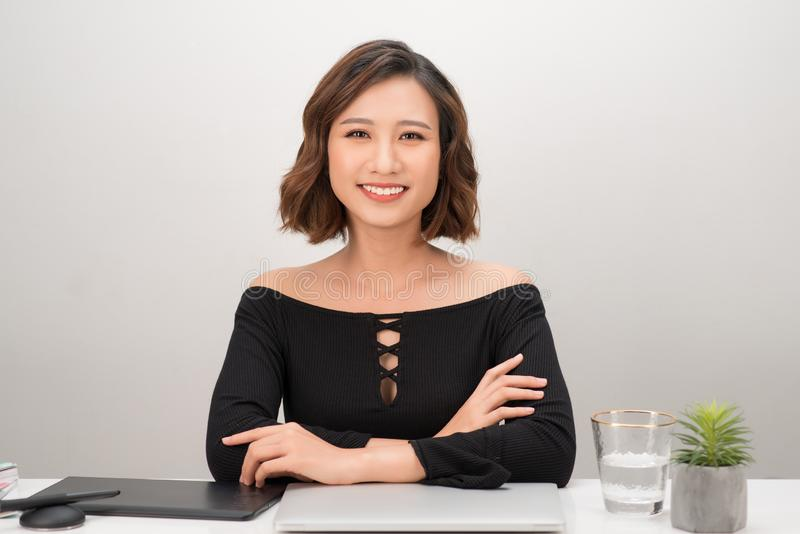 Asian Female designer looking at camera on workplace. Beautiful confident woman sitting at desk with laptop and graphic tablet stock photography
