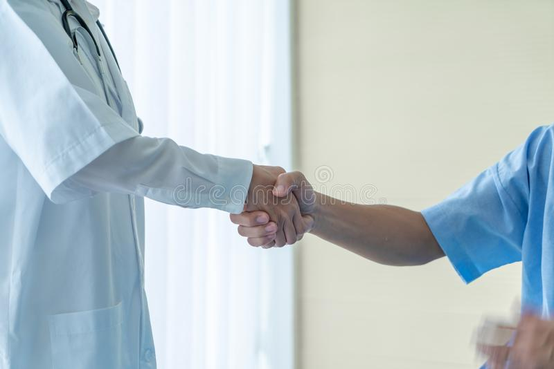 Asian female doctor at the hospital or clinic giving an handshake to hre patient royalty free stock images