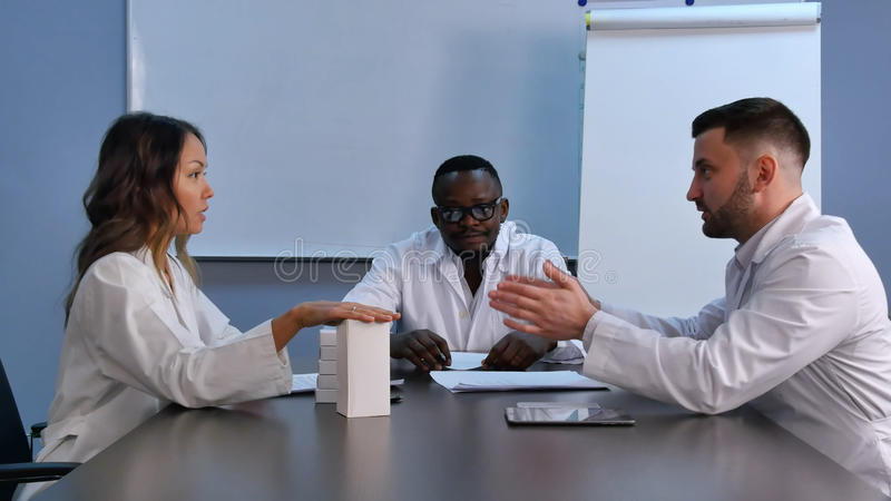 Asian female doctor presenting new pills to colleagues royalty free stock image