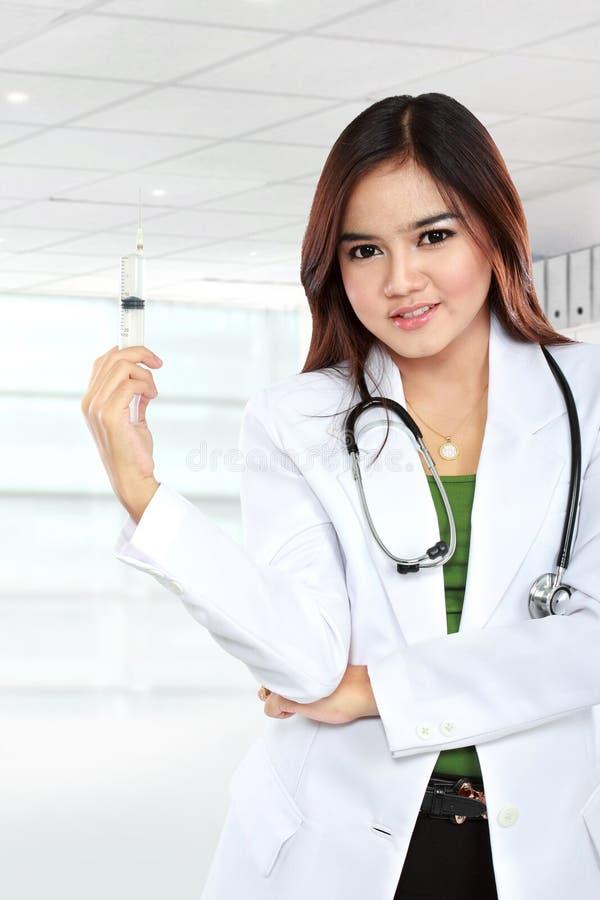 Asian female doctor's wearing a white coat and stethoscope posin. Portrait of asian female doctor's wearing a white coat and stethoscope posing with syringe stock photography