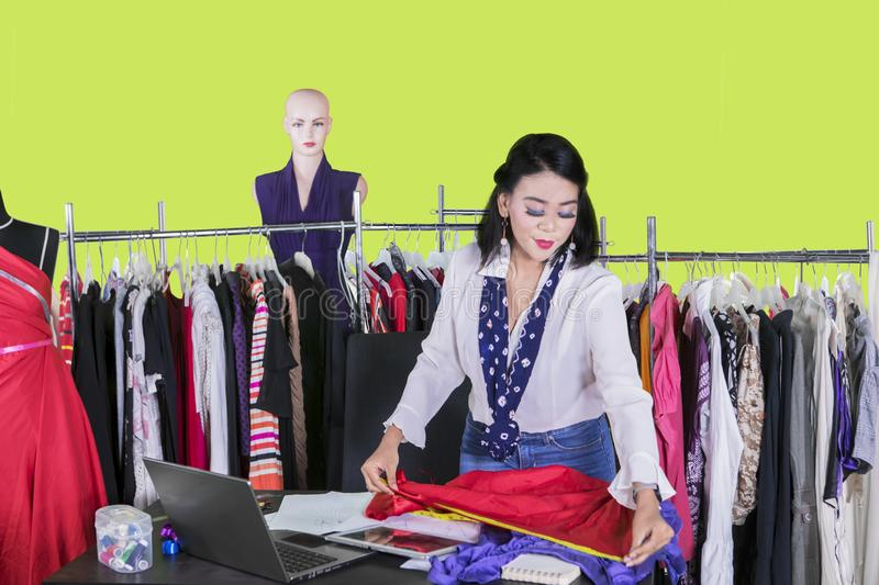 Asian female dressmaker measuring a fabric stock images