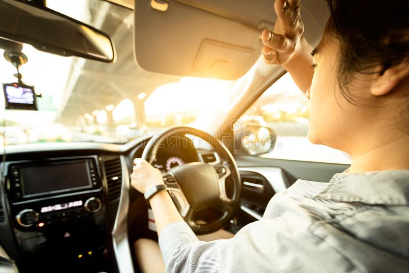 Asian female driver covering face by hand of bright sun,disturbed dazzled by sun light,difficulty in driving,young woman driving. Car feeling hot uncomfortable stock image