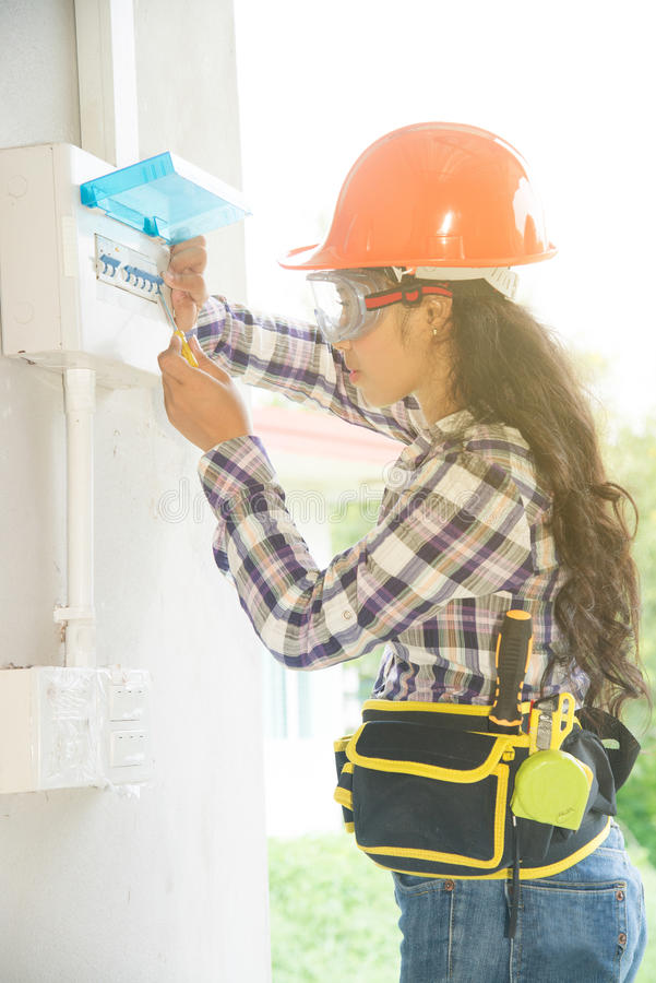 Asian female Electrician or Engineer check or Inspect Electrical system circuit Breaker. Pretty Asian female Electrician or Engineer check or Inspect Electrical stock photo