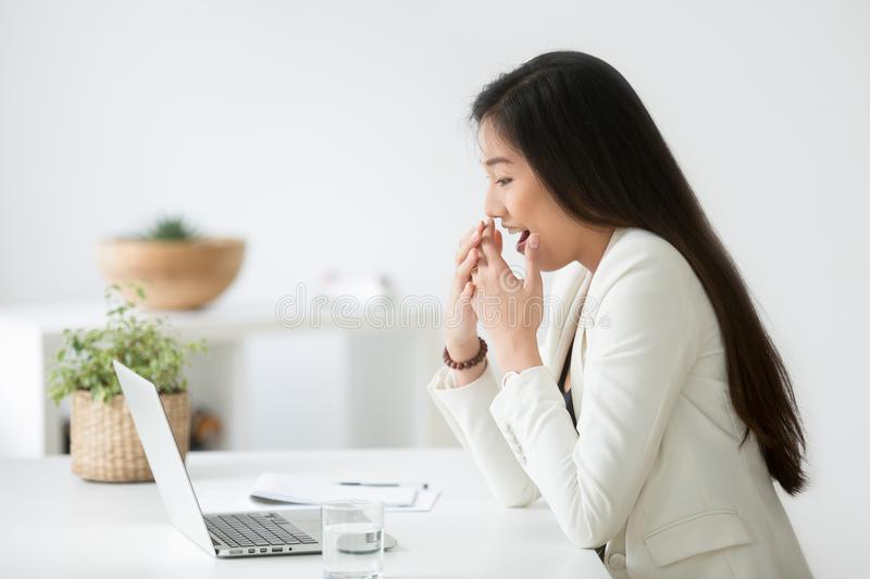 Asian female employee excited with unexpected news. Asian female employee excited with unexpected online lottery win, promotion email, company sales growth on royalty free stock photos