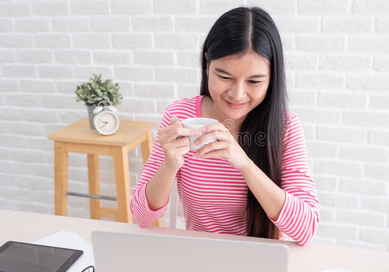 Asian female freelancer smile and drink coffee with relax emotion and looking at laptop screen on table at brick wall stock photo