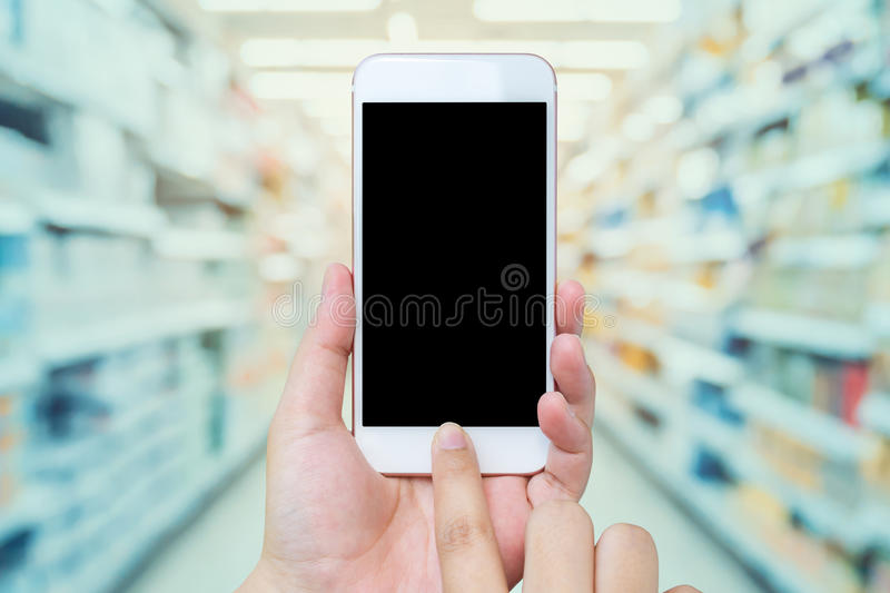 Female hand holding mobile phone with Supermarket background royalty free stock photos