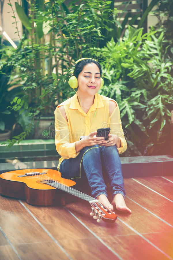 Asian female musician using mobile phone for entertainment. Vintage effect tone. stock image