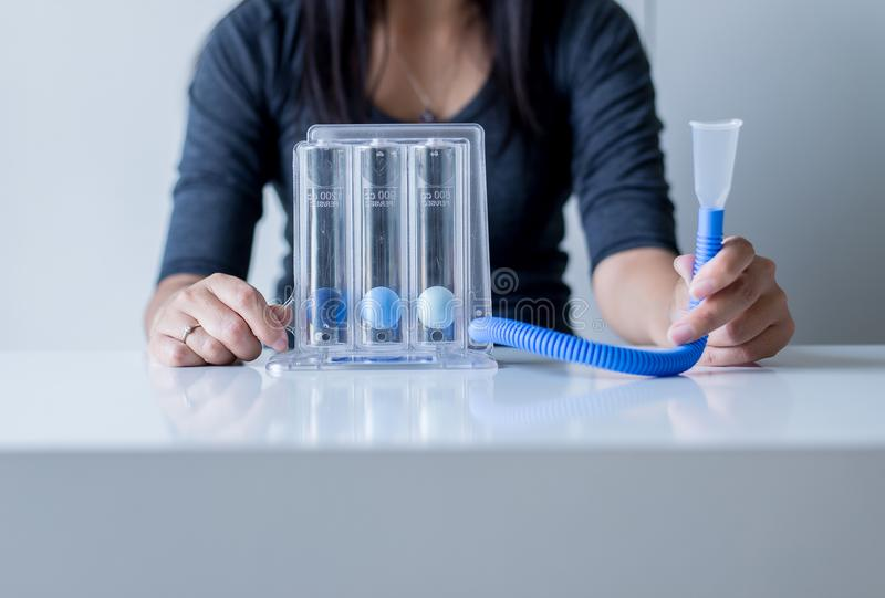 Asian woman patients using incentivespirometer or three balls for deep patient breathing royalty free stock photo