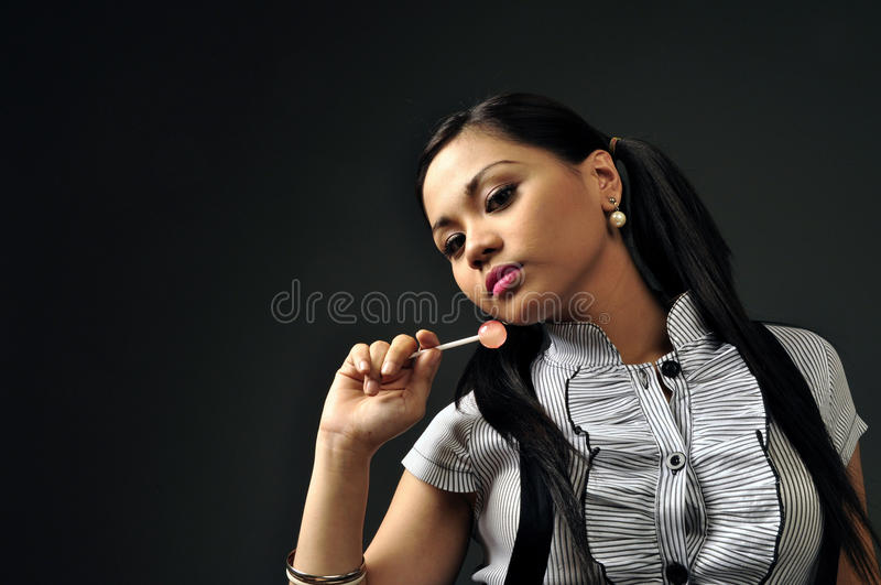 Asian female playing with a lollipop