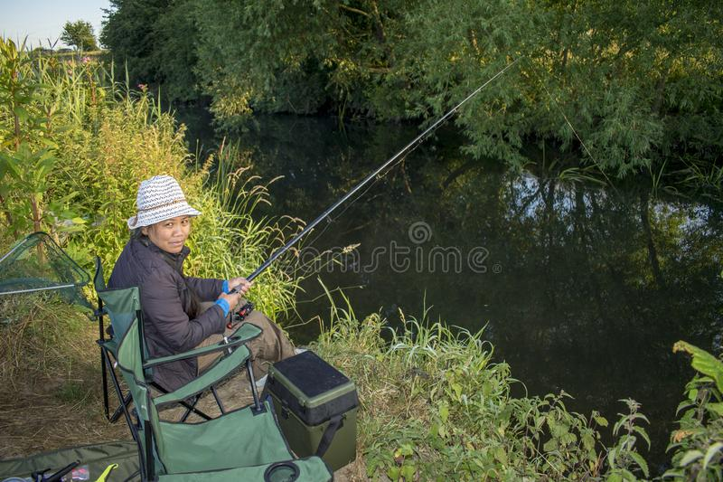 Asian Female River Fishing On A Summer Day. Filipina Woman Fishing On The River Dearne On A Bright Sunny Summers Day In July 2018 stock images